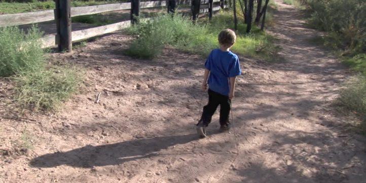 Small Boy Walking Down Dirt Road